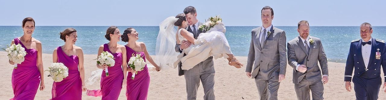 wedding party with groom carrying bride on the beach and the ocean as background