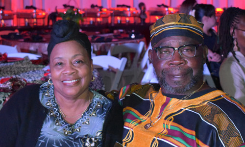 Black Heritage couple smiling at their seats at banquet